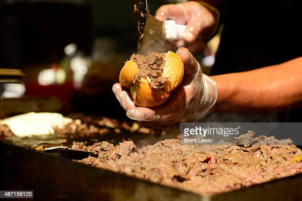 A cook at Large Marge's Philly Cheesesteaks prepares a philly cheesesteak sandwich during the third day of A Taste of Colorado on September 6 2015 in...