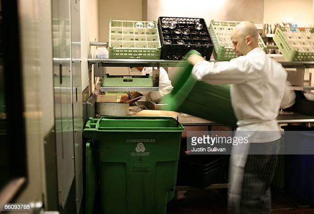 A cook at MoMo's restaurant empties food scraps into a larger recycling container April 21 2009 in San Francisco California Norcal Waste Systems is...