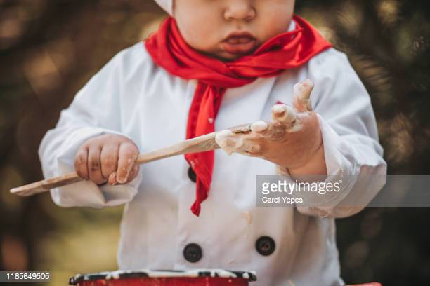 cook boy licking spoon outdoors - carol cook stock pictures, royalty-free photos & images