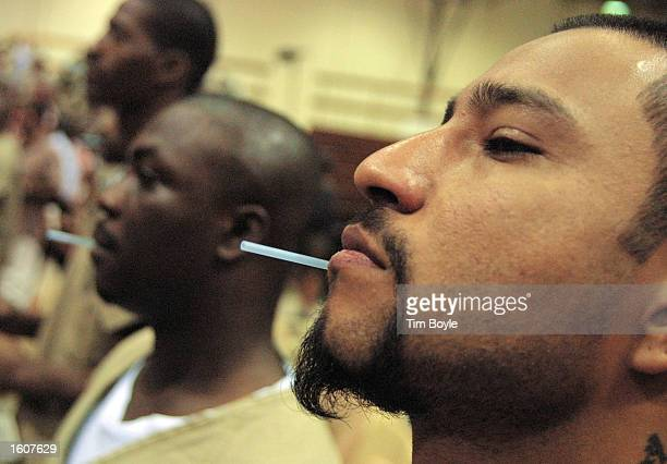 Cook County Jail detainees take an AIDS test August 7 2001 at the jail in Chicago Illinois Rev Jesse Jackson along with several other ministers...