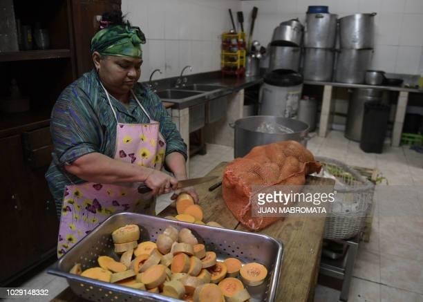 A cook cuts butternut squash while preparing dinner at Los Piletones soup kitchen run by Argentine social activist Margarita Barrientos in Villa...