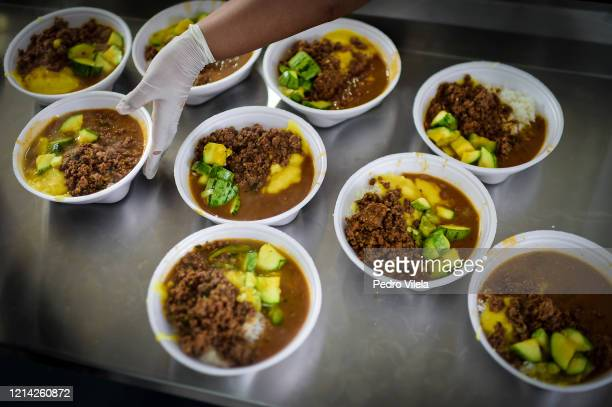 Cook from the Favela Aglomerado da Serra residents' association prepares meals that are being delivered to the poorest residents on May 20, 2020 in...