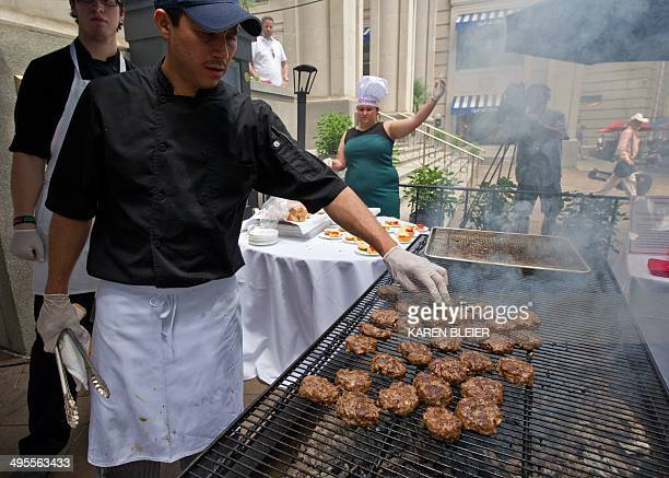 A cook grills grasshopper burgers June 4 2014 during a global Pestaurant event sponsored by Ehrlich Pest Control held at the Occidental Restaurant in...