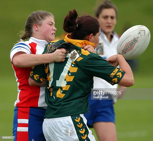 Cook Island player Stephanie Utanga gets the ball knocked out of her hands by Stacey Greenwood during the 2002 Womens Rugby League World Cup between...