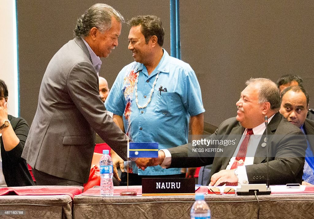 Cook Islands Prime Minister Henry Puna (L) shakes hands with Nauru's President Baron Waqa (R) as Palau's President Tommy Remengesau (C) looks on during the Smaller Islands States Leaders meeting as part of the Pacific Islands Forum in Port Moresby, Papua New Guinea, on September 7, 2015. Vulnerable Pacific island nations will this week send the world an urgent plea for action on climate change at crunch talks in Paris later this year. Some Pacific Islands Forum (PIF) countries lie barely a metre (three feet) above sea level and fear they will disappear beneath the waves without drastic intervention from major polluters. AFP PHOTO / Ness KERTON