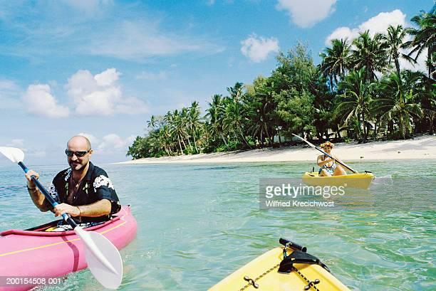 Cook Islands, Rarotonga, couple kayaking in sea by deserted beach