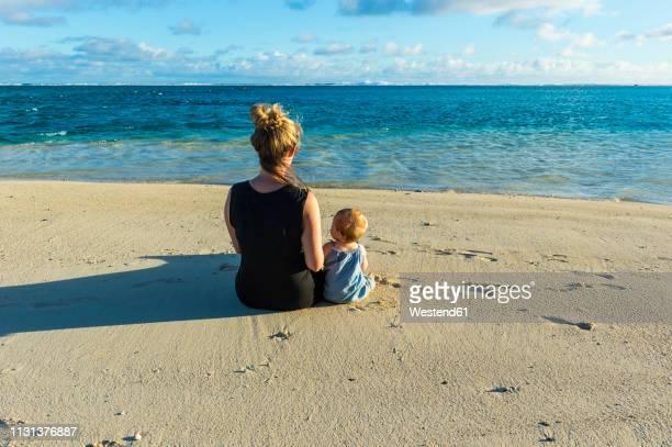 cook islands, rarotonga, woman sitting with her baby on a white sand beach - rarotonga foto e immagini stock