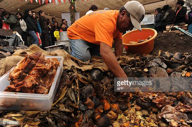 A cook picks potatos from a Pachamanca a traditional meal cooked inside a hole made on the ground and covered with hot rocks at Mistura Fair 2009 an...