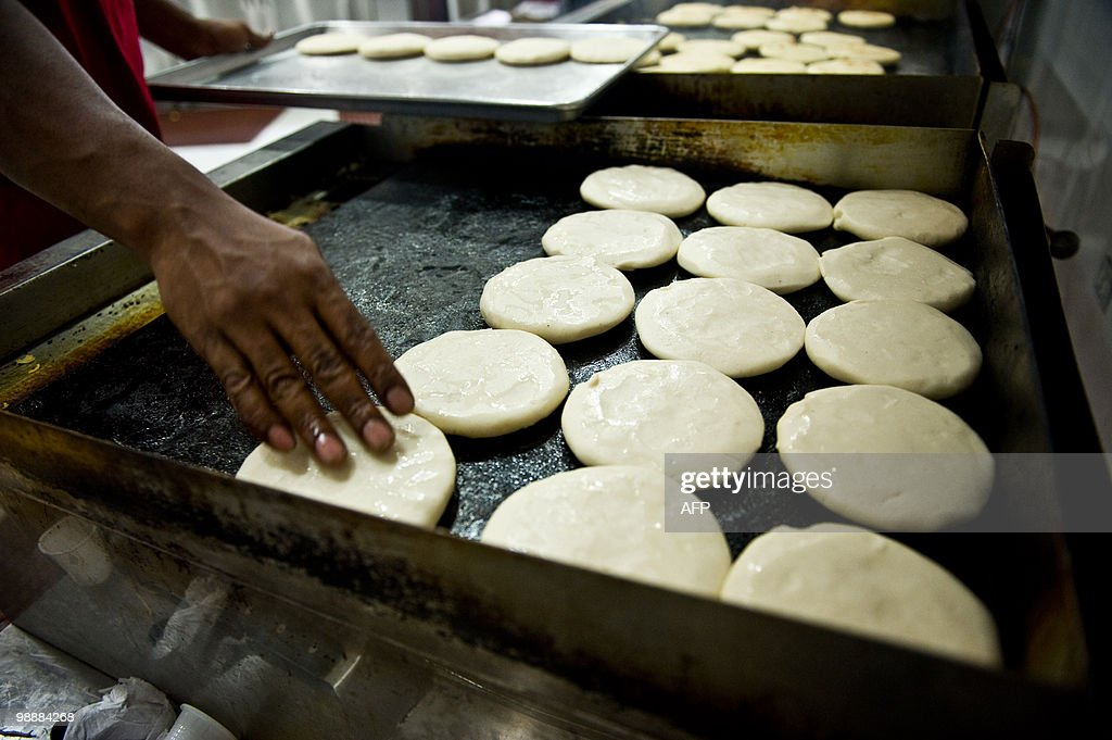 ABREU --- A cook prepares 'arepas' at a Socialist Arepera restaurant in Caracas on April 30, 2010. The 'Socialist Areperas' are one of the new state retail system inaugurated by President Hugo Chavez. An arepa is a bread made of corn popular in Venezuela and Colombia. AFP PHOTO / Miguel Gutierrez