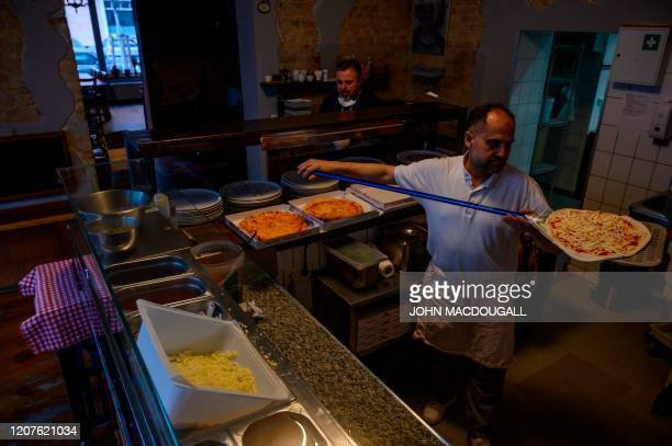 A cook prepares pizzas for delivery in an Italian restaurant in Berlin's Prenzlauer Berg district on March 18 2020 The manager to reduce any risk of...