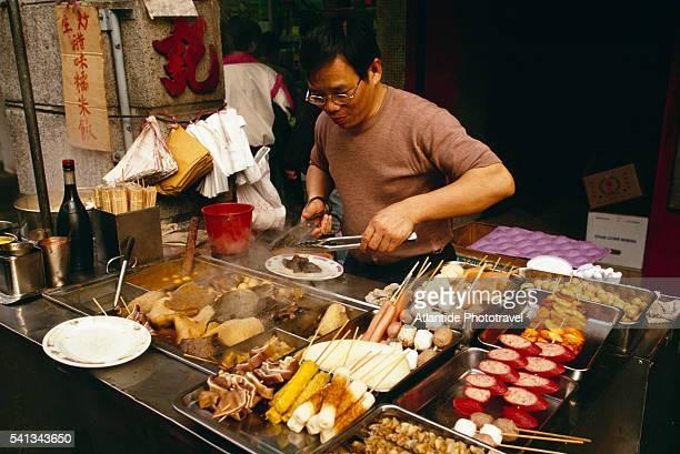 cook preparing food in rua do almirante sergio - rua stock-fotos und bilder