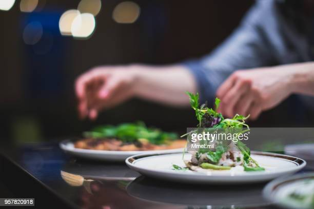 cook preparing many plates in a restaurant kitchen. catering. caterer - food stock pictures, royalty-free photos & images