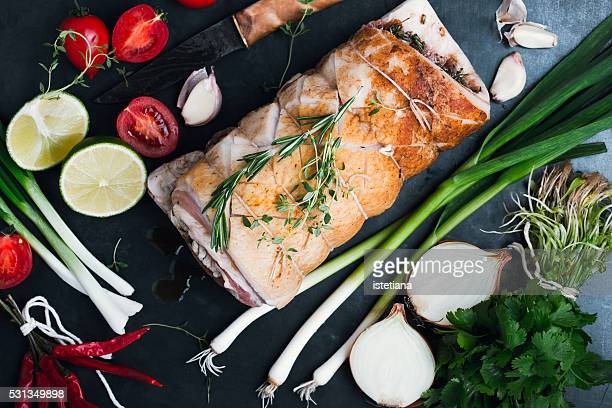 Cook preparing rolled pork belly. Raw meat and vegetables on grey rustic table, top view