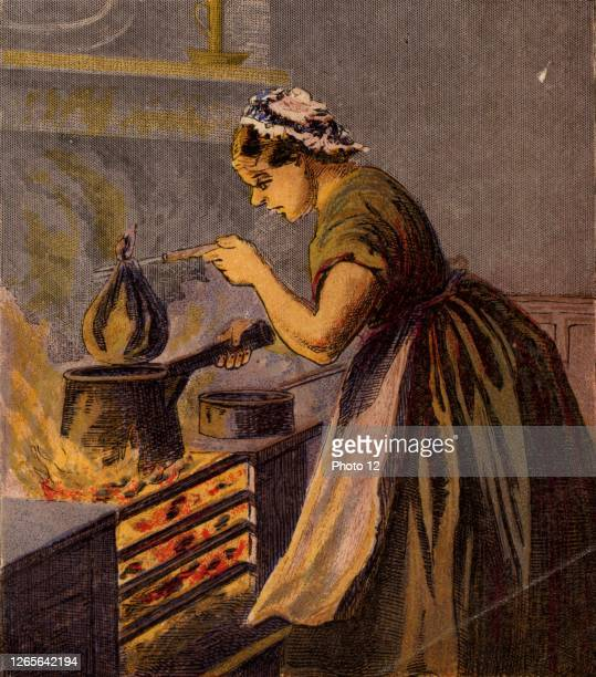 Cook putting a suet pudding wrapped in a cloth in a saucepan of hot water to boil on a typical small kitchen range. Kronheim chromolithograph from a...