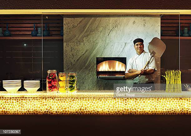 cook standing by his pizza oven - pizza oven stock photos and pictures
