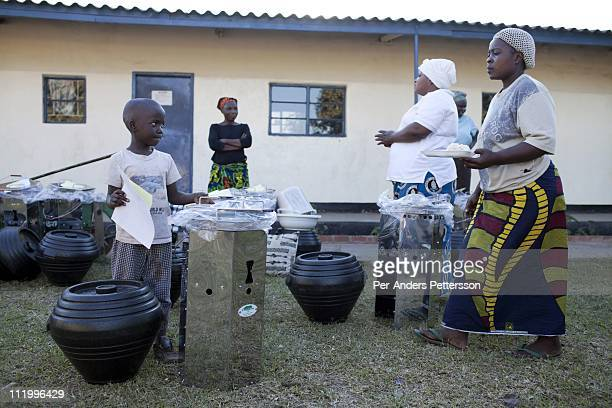 Cook stoves supplied by Clean Development Mechanism are demonstrated and handed out to families on June 14 in Lusaka Zambia CDM is one of the...
