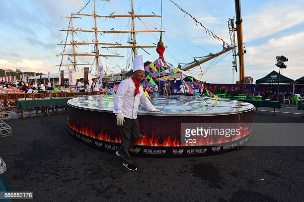 A cook touches the large cauldron where 24 kinds of seafood are cooked during the 8th Qingdao International Sailing Week Qingdao International Marine...