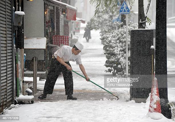 A cook tries to remove snow from the sidewalk in front of his restaurant in downtown Tokyo on February 8 2014 Heavy snow struck Tokyo and other areas...