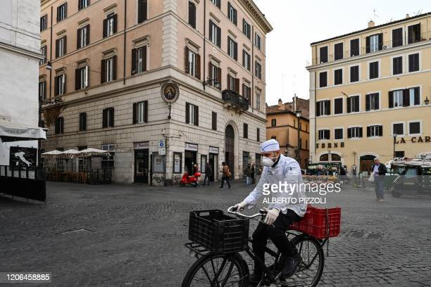 A cook wearing a respiratory mask as part of precautionary measures against the spread of the new COVID19 coronavirus rides a bicycle across a...