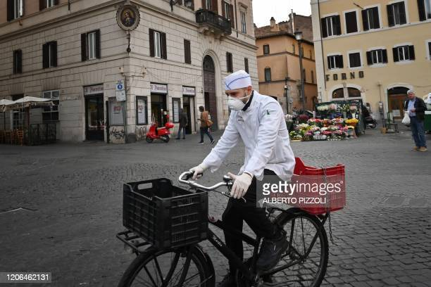 TOPSHOT A cook wearing a respiratory mask as part of precautionary measures against the spread of the new COVID19 coronavirus rides a bicycle across...