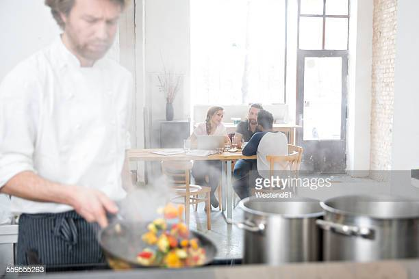 Cook working in kitchen of his restaurant while guests communicating in the background