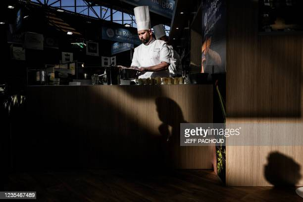 Cook works in a booth of the SIRHA International Hostel, Restaurant and Food fair in Eurexpo hall in Chassieu, near Lyon, central eastern France, on...