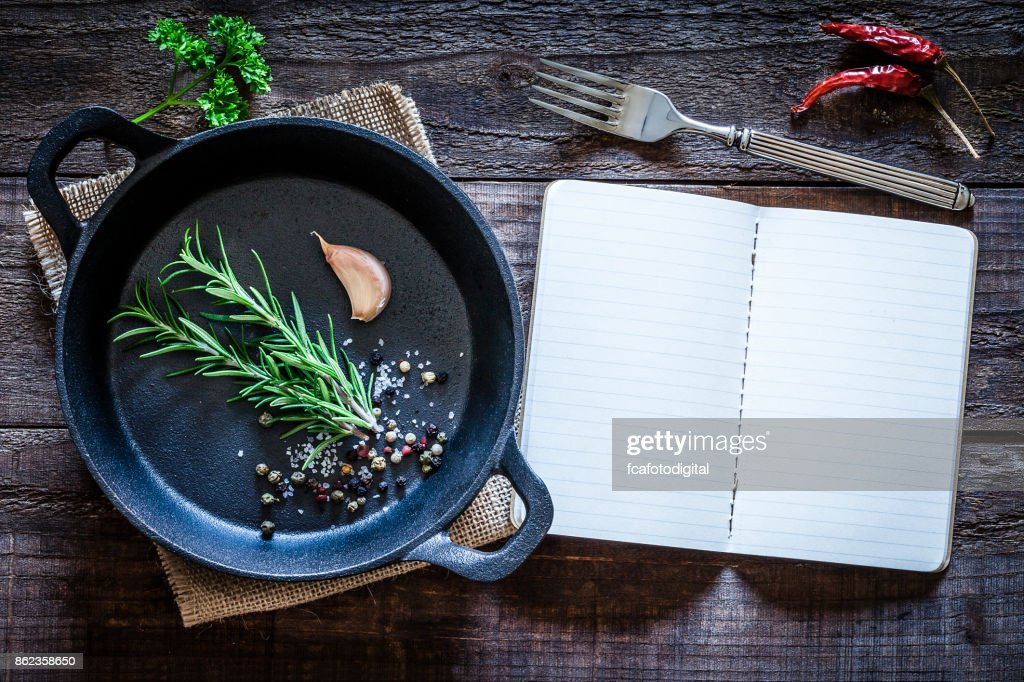 Cookbook and cast iron pan with some herbs on wooden table : Foto stock