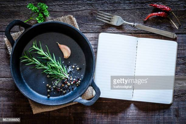 cookbook and cast iron pan with some herbs on wooden table - food dressing stock pictures, royalty-free photos & images