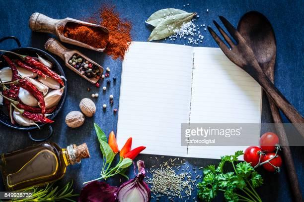 livro de receitas com especiarias e ervas na mesa da cozinha escura - receita - fotografias e filmes do acervo