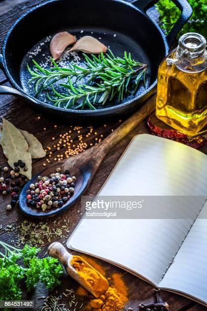kochbuch mit gewürzen und kräutern auf dunklen küchentisch - kochbuch stock-fotos und bilder