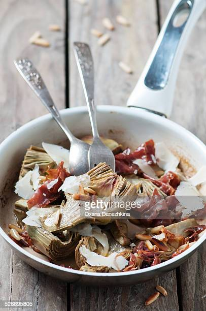 Cooked artichoke with pine nuts, cheese and ham