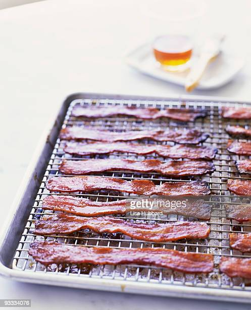 cooked bacon strips on wire rack - cooling rack stock photos and pictures