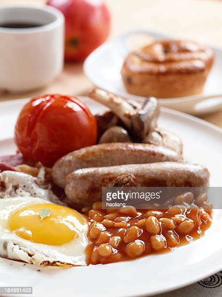 Cooked breakfast of fried egg baked beans sausage and tomato