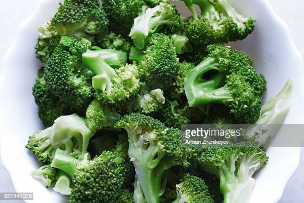 Cooked broccoli in white colander