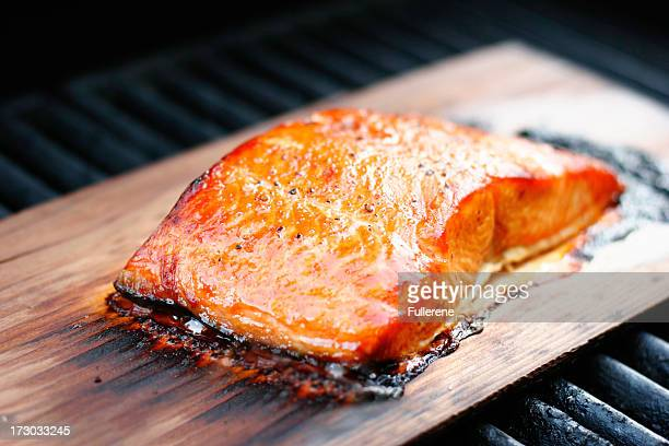 cooked cedar plank salmon on wood - smoked food stock photos and pictures