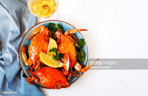 cooked crabs on black plate and glass of white wine - boiled stock pictures, royalty-free photos & images