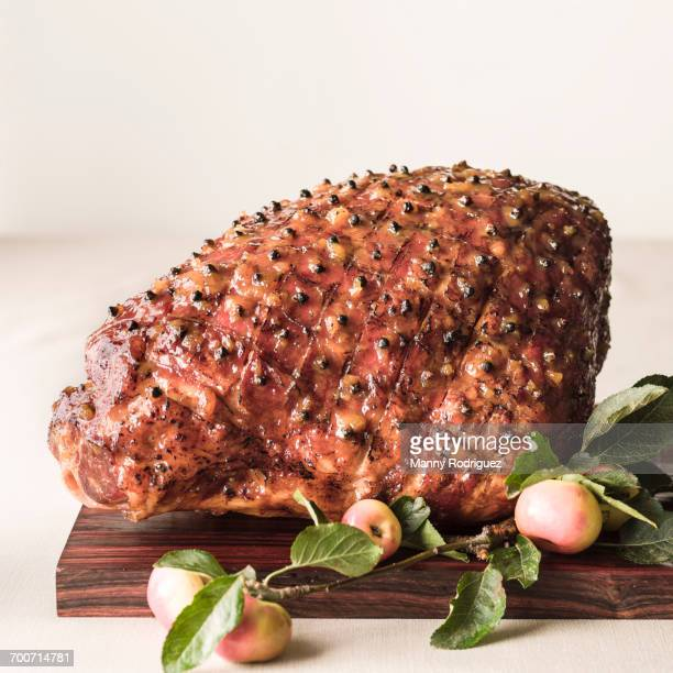 cooked glazed ham on wooden cutting board - glazed ham stock pictures, royalty-free photos & images