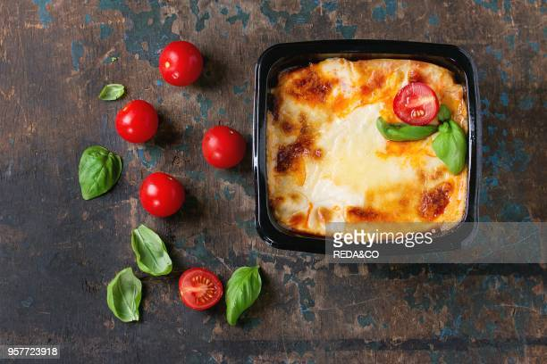 Cooked meat lasagna in black plastic box served with fresh cherry tomatoes and basil leaves over old dark wooden textured background Market...