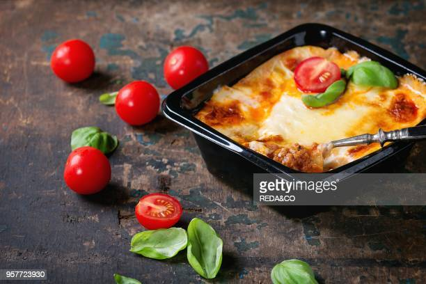 Cooked meat lasagna in black plastic box served with vintage fork fresh cherry tomatoes and basil leaves over old dark wooden textured background...