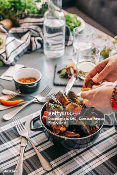 cooked mussels with cherry tomatoes and green spices - appetiser stock photos and pictures