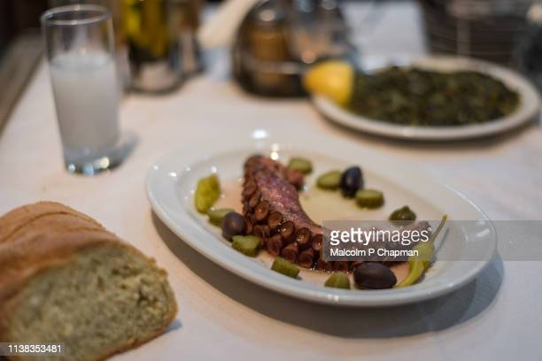 cooked octopus tentacle served with olives, spinach, ouzo and bread, eresos, lesvos, greece - lesbos stock pictures, royalty-free photos & images