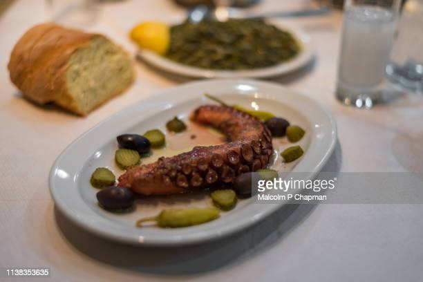 Cooked Octopus tentacle served with olives, spinach, ouzo and bread, Eresos, Lesvos, Greece