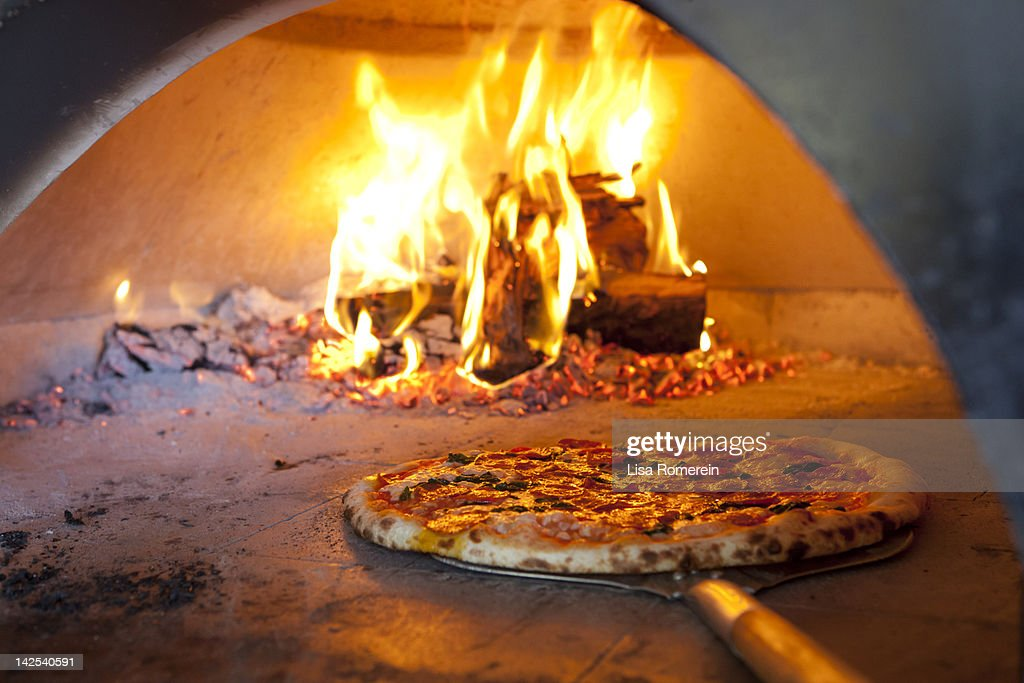 Cooked pizza coming out of hot brick oven : Stock Photo