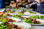 Cooked Roast Beef, Fresh Salad And Tomatoes Served On White Plates. Cooking Master Class, Workshop with People Learning How to Cook Around the Table