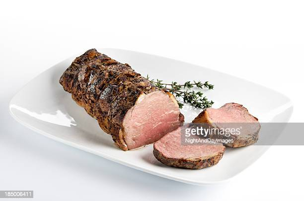 cooked roast beef on a white plate - beef stock pictures, royalty-free photos & images