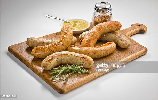 Cooked sausages on cutting board with mustard