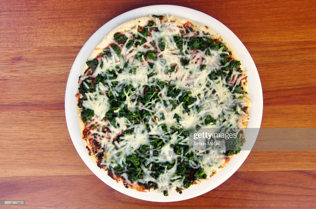 Cooked spinach and cheese frozen pizza : Stock Photo