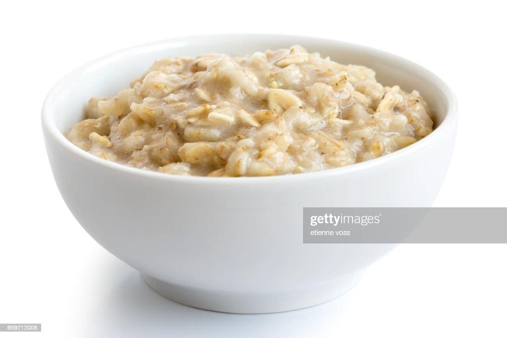 Cooked whole porridge oats in white ceramic bowl isolated on white. : Stock Photo