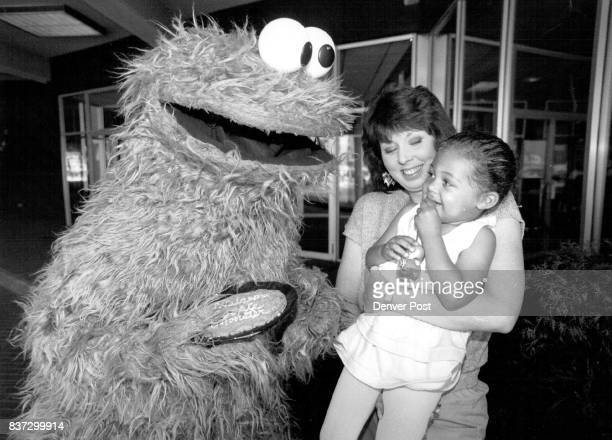 Cookie Monster stops to say hello to 2 year-old Raven Patterson outside of Holiday Inn at 15th and Glenarm. Raven is being held up by her mother...