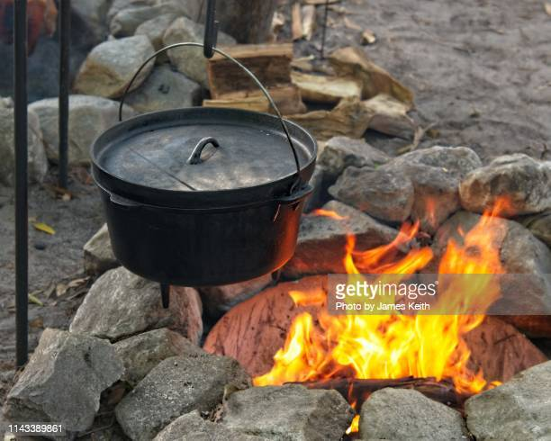 cooking a meal in the pioneer way with a metal kettle over an open fire. - 大釜 ストックフォトと画像